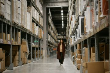 woman walking down a warehouse aisle