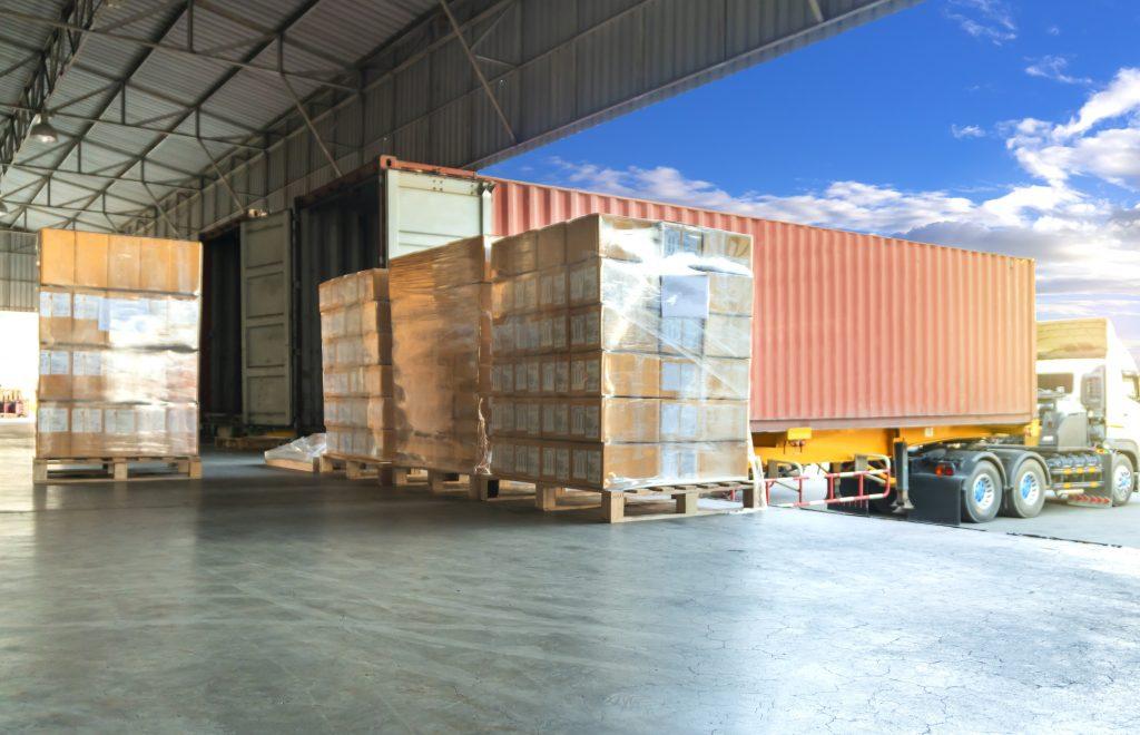 Freight transportation by trucks, trucks trailer docking loading cargo at warehouse
