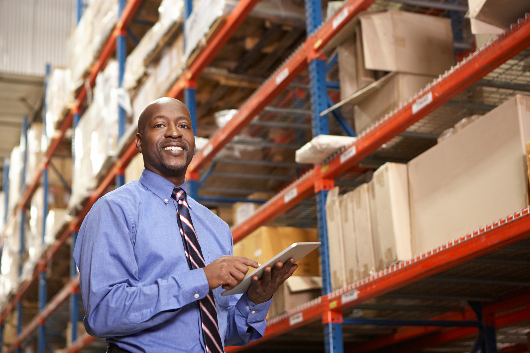 Businessman With Digital Tablet In Warehouse Looking At Camera Smiling